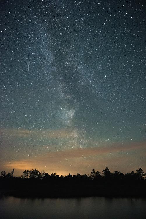 Starry sky with Milky Way and bog pool in raised bog at night, with slight touch of light pollution from Riga, Kemeri National Park (Ķemeru Nacionālais parks), Latvia Ⓒ Davis Ulands   davisulands.com