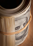 Extreme close up of roll of currency held together with a rubber band with a $100 bill on top