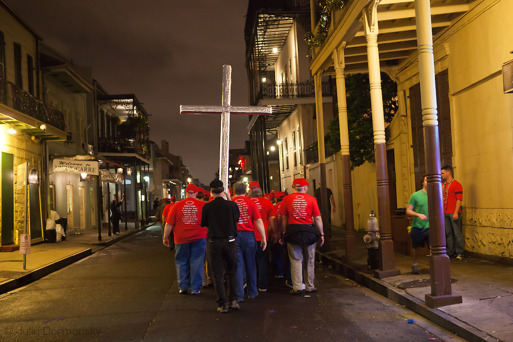 A group of men in a fundamentalist religous group wearing Jesus tee- shirts marches with a cross through the French Quarter in New Orleans on Fat Tuesday when the area is full of people drinking alchol on the street.  Gras 2011 in New Orleans is expected to be have the largest attendance of all time due to the dates overlapping with college spring break. Mardi Gras also known as Carnival begins on or after Epiphany and ending on the day before Ash Wednesday.