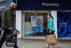 © Licensed to London News Pictures. 26/10/2021. London, UK. Shoppers walk past a 'Free NHS Flu Jab' poster displayed in Boots pharmacy in Wood Green, north London. People are being urged to get their flu jab ahead of the winter as figures from the drug maker Reckitt suggest that the cold and flu season will be worse this year than normal. Health Secretary Sajid Javid is considering making flu jabs mandatory for all NHS staff.   Photo credit: Dinendra Haria/LNP