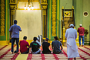 17 DECEMBER 2012 - SINGAPORE, SINGAPORE: Men gather for prayers in the Sultan Mosque in Singapore. The Sultan Mosque is the focal point of the historic Kampong Glam area of Singapore. Also known as Masjid Sultan, it was named for Sultan Hussein Shah. The mosque was originally built in the 1820s. The original structure was demolished in 1924 to make way for the current building, which was completed in 1928. The mosque holds great significance for the Muslim community, and is considered the national mosque of Singapore. It was designated a national monument in 1975.     PHOTO BY JACK KURTZ