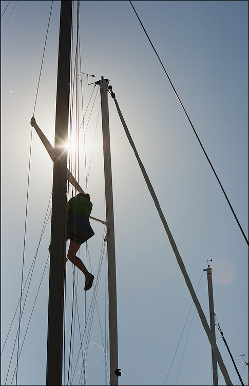 Climbing to make sure the ropes for the headsail and the mainsail are ready and working for the morning Regatta.