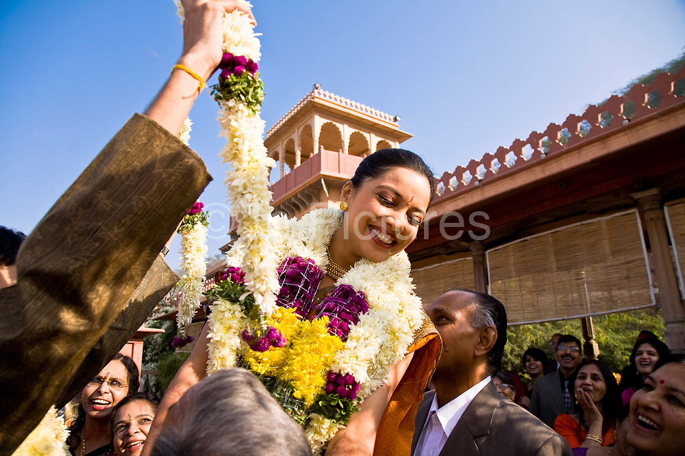 A Hindu bride, Shweta Singhal has three garlands of flowers placed around her neck by her newly wed husband in a ceremony known as Jaimaal, as guests and family of the couple look on in happiness, Neemrana Fort Palace, Rajasthan India.