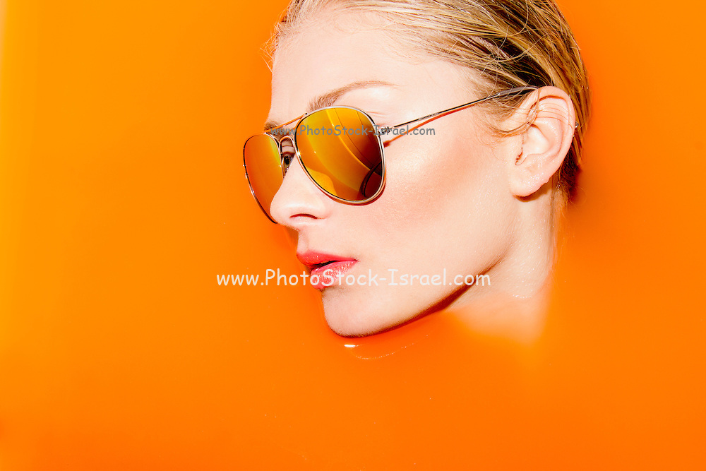 Woman with sunglasses submerged in water