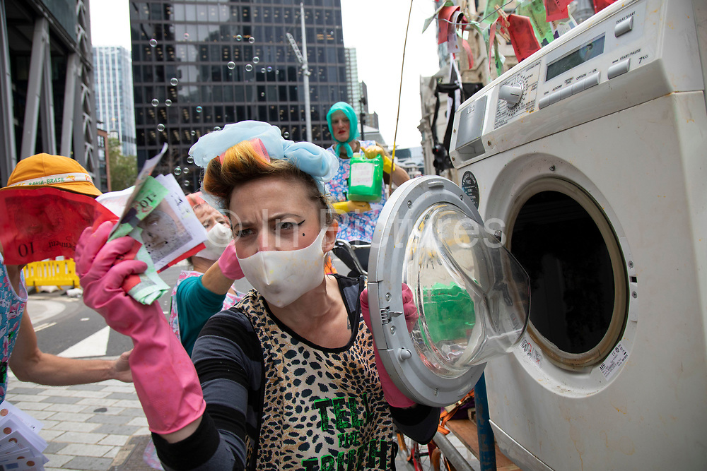 Extinction Rebellion 'Dirty Scrubbers' old fashioned washer women in curlers wash and launder their 'dirty money' and greenwash stains in the City of London financial district in a performance designed to highlight the corruption of big business and banking on 9th September 2020 in London, United Kingdom. The activists shouted out for people to come from the banks and to bring their dirty money to be cleaned in their washing machines. Extinction Rebellion is a climate change group started in 2018 and has gained a huge following of people committed to peaceful protests. These protests are highlighting that the government is not doing enough to avoid catastrophic climate change and to demand the government take radical action to save the planet.