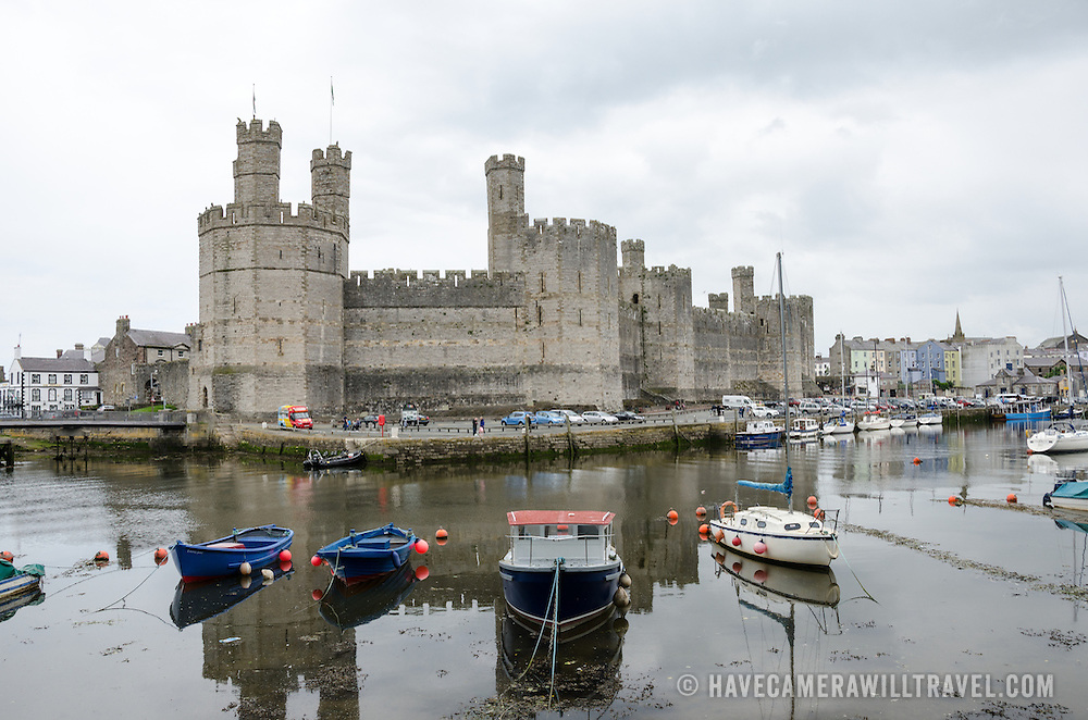 A wide view of the rievr and Caernarfon Castle in northwest Wales. A castle originally stood on the site dating back to the late 11th century, but in the late 13th century King Edward I commissioned a new structure that stands to this day. It has distinctive towers and is one of the best preserved of the series of castles Edward I commissioned.