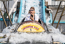 © Licensed to London News Pictures. 08/08/2020. Brighton, UK. Members of the public take a ride on an attraction on the Brighton Palace Pier in Brighton and Hove. The seaside resort is getting ready for the second  day of a heatwave that is hitting the UK. Temperatures are reaching the high 30C's on the South Coast. Photo credit: Hugo Michiels/LNP