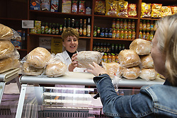 Shop Assistant serving customer in Polish Delicatessen,