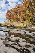 Mill Creek erodes ancient limestone, upstream of Lower Falls in Cataract Falls State Recreation Area, an hour southwest of Indianapolis, near Cloverdale, Indiana, USA. Autumn foliage colors were brilliant but water volume was low for this photo in mid October 2015. The park's limestone bedrock formed millions of years ago from skeletal remains of marine organisms (such as coral, forams and molluscs) when the region was covered by a large shallow ocean.