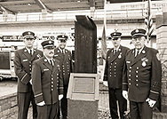 Bellmore, New York, USA. 11th September 2015. L-R, Bellmore Fire Dept. Chief DANIEL HOLL, Pastor and Chaplain JAMES BARNUM, 1st Deputy VINCENT MONTERA, 2nd Deputy TOM STOERGEN, and Chaplain DENNIS RICH stand next to a monument that's a piece of structural steel from the Twin Towers, during the Bellmore Memorial Ceremony for 3 Bellmore volunteer firefighters and 7 residents who died due to 9/11 NYC terrorist attacks. Elevated platform of Bellmore LIRR Station is in background.