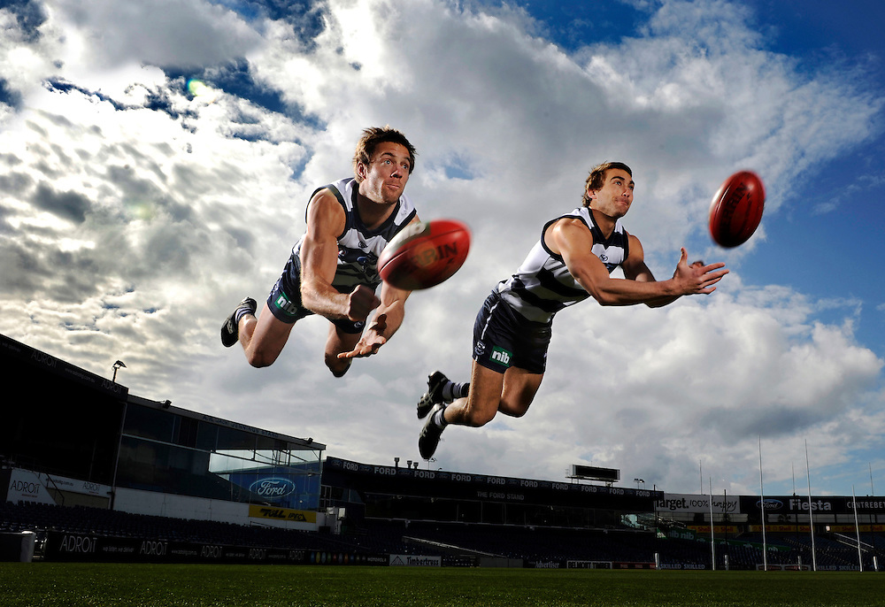 Geelong Cats footballers Joel Corey, left, and Corey Enright show all their usual flair and athleticism when leaping simultaneously in the air while executing a diving handpass for the camera.<br /> The picture backed up the feature story during their 2009 grand final week on how they did everything together. They were inseparable after they became flat mates living together and loved how their names have always caused confusion with everybody in the football world.<br /> Over a decade later, the former flatmates are both premiership players and duel All-Australians. (Copyright Michael Dodge/Herald Sun)