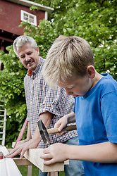 Grandfather grandson working together wood
