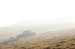 © Licensed to London News Pictures. 13/03/2014. Mynydd Epynt, Powys, Wales,UK. A vehicle climbs a hill to the high moorland in the mist. Photo credit : Graham M. Lawrence/LNP