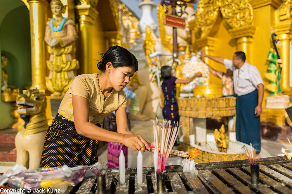 07 JUNE 2014 - YANGON, YANGON REGION, MYANMAR: A woman makes merit and prays at an alter for people born on Tuesdays at Shwedagon Pagoda. People pray at alters and chapels dedicated to the day of the week they were born on in Theravada Buddhism. Shwedagon Pagoda is officially called Shwedagon Zedi Daw and is also known as the Great Dagon Pagoda and the Golden Pagoda. It's a 99 metres (325ft) gilded pagoda and stupa located in Yangon. It is the most sacred Buddhist pagoda in Myanmar with relics of the past four Buddhas enshrined within: the staff of Kakusandha, the water filter of Koṇāgamana, a piece of the robe of Kassapa and eight strands of hair from Gautama, the historical Buddha.   PHOTO BY JACK KURTZ