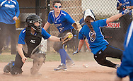 Middletown, New York - A catcher reaches to tag a sliding baserunner during a varsity girls' softball game on April 25, 2014.