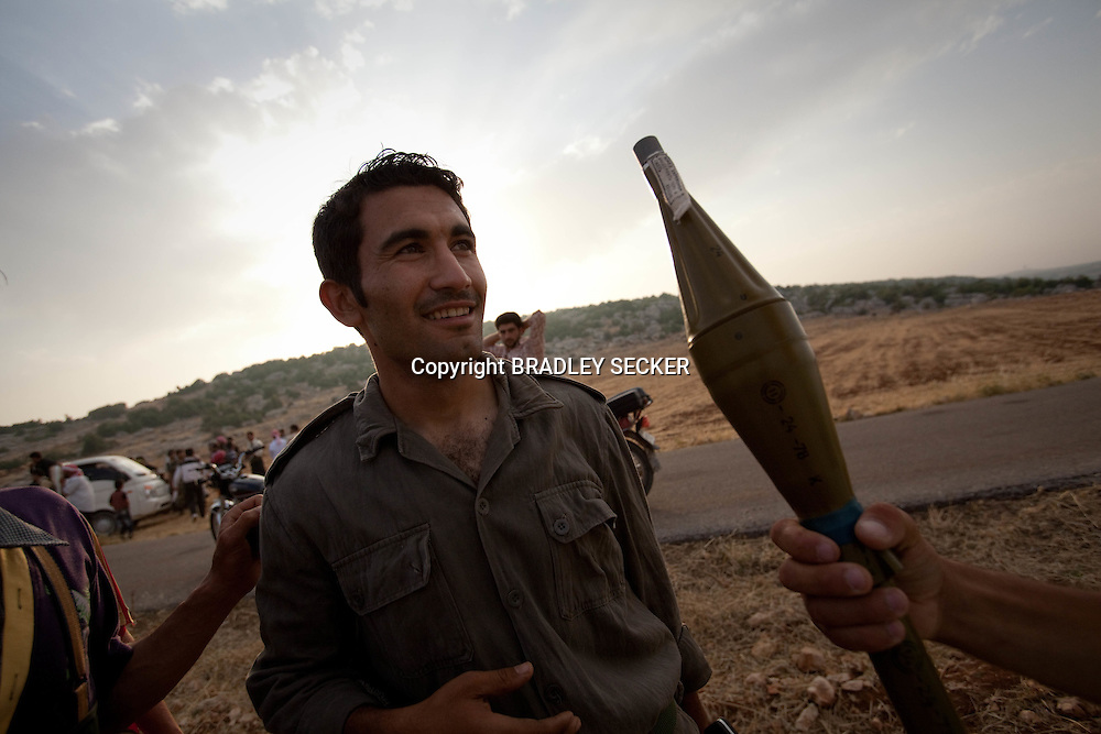 FSA soldiers inspect their arsenal as one soldier passed an RPG to another. Idlib province in Syria's northwest is one of the few areas in Syria which is currently under FSA control, although this control is patchy and ever shifting. Rural Idlib, Syria. 16/06/2012
