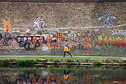 Person walking alongside a grafitti covered wall beside a canal in East London.