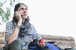 Teenage male hiker talking on mobile phone and holding an apple, Bavaria, Germany