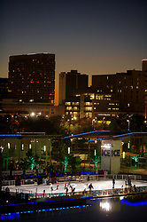Stock photo of skaters on the ice skating rink at night during the holiday season