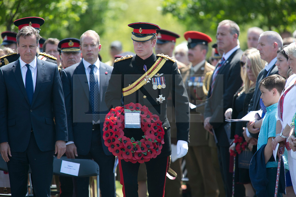 © Licensed to London News Pictures. 11/06/2015. National Memorial Arboretum, Alrewas, Staffordshire, UK. The service to mark the Rededication of the Bastion Memorial. The memorial was begun in Helmand Province in 2006, deconstructed in 2014 and now replicated at the National Memorial Arboretum in Staffordshire. Around two thousand people took part in the service including HRH Prince Harry, the Prime Minister David Cameron and senior members of the Armed Forces.  PRINCE HARRY Laying his wreath. Photo credit : Dave Warren/LNP