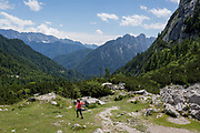 A child plays with a mountain view in the distance at the top of Vrsic Pass in the Slovenian Julian Alps, on 22nd June 2018, in Triglav National Park, Slovenia.