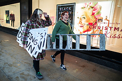 """© Licensed to London News Pictures . 01/12/2018. Manchester , UK . Staff take down """" Closing Down """" signs from the Kendal's House of Fraser department store on Deansgate in Manchester City Centre after a new rental agreement was secured with the landlord . Photo credit : Joel Goodman/LNP"""