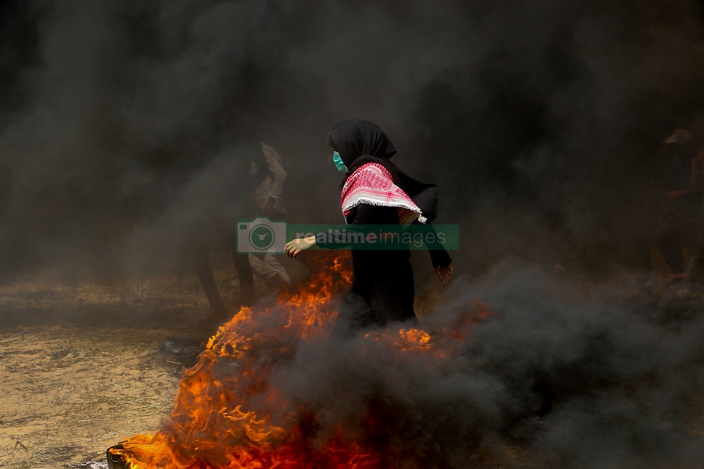 """April 13, 2018 - Clashes erupt between Palestinian demonstrators and Israeli Security Forces east of the southern city of Khan Yunis, near the Gaza Strip border with Israel. Palestinians were demonstrating as part of the """"Long March of Return"""" events, for the third consecutive Friday. A number of Palestinians were injured by live ammunition and tear gas fired at them by Israeli soldiers. The Long March of Return is a series of mass protests, along the Israel-Gaza border, intending to highlight the right to return for Palestinian refugees and their descendants to their ancestral lands in what is now Israel, and to call for the lift of the more of a decade-long blockade imposed by Israel on the Gaza Strip (Credit Image: © Ahmad Hasaballah/IMAGESLIVE via ZUMA Wire)"""