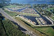 """Nederland, Noord-Holland, Abcoude, 25-09-2002; pal naast autosnelweg A2 is Buitenborgh gebouwd: """"luxe vrijstaande recreatievilla's met open vaarwater naar de Vinkenveensche Plassen (citaat makelaarsbrochure); hoewel het bestemmingsplan (streekplan) bouw in dit deel vh Groene Hart verbiedt, mochten deze woningen wel gebouwd omdat ze (op papier) niet permanent bewoond worden; recreatiewoning, tweede huis, vakantiewoning, planologie, verloedering van het landschap, milieu, toerisme, mobiliteit; zie ook andere foto van deze lokatie;..right next to motorway A2: """"luxury detached villas with recreational waters and direct connection with nearby lake"""" (quotation from estate agent brochure); although the planning permission / zoning in this part of the 'Green Heart' prohibits such housing, the villas could be built because they (on paper) are not permanently inhabited; recreation, second home, holiday home, planning, degradation of the landscape, environment, tourism, mobility, see other photos of this location;<br /> luchtfoto (toeslag), aerial photo (additional fee)<br /> foto /photo Siebe Swart"""