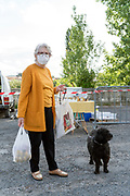 woman with dog food shopping at an outdoors farmers market during the Covid 19 crisis and lockdown France Limoux April 2020