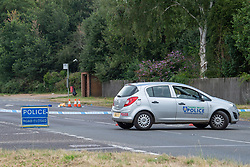 © Licensed to London News Pictures. 27/07/2021. Stoke Poges, UK. A police vehicle forms a cordon at the scene on Bells Hill in Stoke Poges, Buckinghamshire, following an assault on Monday 26 July at approximately 21:30BST. A man in his twenties suffered a serious leg injury following the assault which is understood to have involved a machete. Two men, aged 19 and 21, and a 20-year-old woman have been arrested on suspicion of section 18 wounding with intent. Photo credit: Peter Manning/LNP