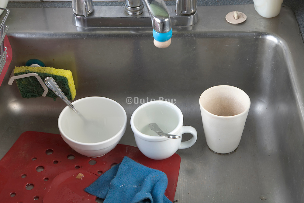 kitchen sink with dirty cups kitchen utensils and sponge