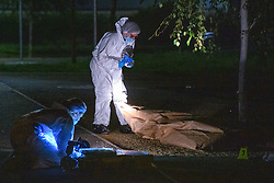 © Licensed to London News Pictures. 15/08/2021. Slough, UK. Forensic investigators gather evidence at the scene following a double stabbing in Cippenham, Slough. Emergency services were called at approximately 17:00BST on Sunday 15/08/2021 to the Eltham Avenue area of Slough to reports that two male teenagers had been assaulted during an altercation between a number of youths. Both were taken to hospital with stab wounds. Photo credit: Peter Manning/LNP