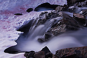 Water cascades down over rocks and under a snow field at the outlet of a lake in an alpine basin in Glacier Peak Wilderness, Washington.