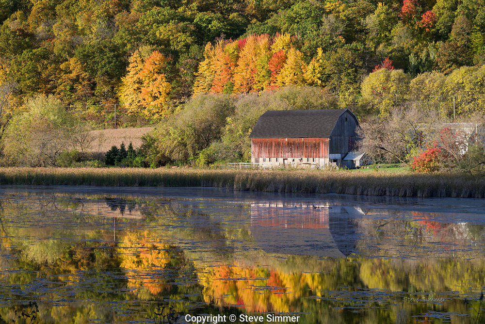 I photographed this barn in the subdued colors of spring. On this return visit, I found it surrounded with spectacular fall color. A calm morning to give a clear reflection was a bonus.