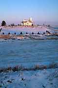 Distant church on hill centered behind field and cemetery with snow on ground. Garden City Iowa USA