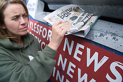 Woman putting old newspaper into a recycling bank,