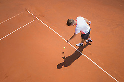 Young male tennis player preparing to serve the ball on sunny red tennis court, Bavaria, Germany
