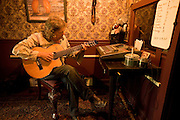 A North Carolina guitar and gun maker plays one of his creations in a recording studio at his home