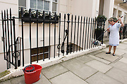 A maid uses a mop and bucket to wash down paintwork and railings at an exclusive address in Chester Square, Belgravia, SW1.