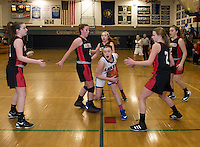 Inter Lakes' Margaux Dickinson charges through Moultonboro's Liz Eaton and Zoe Norton during NHIAA Division III Basketball on Wednesday evening.  (Karen Bobotas/for the Laconia Daily Sun)
