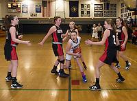 Inter Lakes' Margaux Dickinson charges through Moultonboro's Liz Eaton and Zoe Norton during NHIAA Division III Basketball on Wednesday evening.  (Karen Bobotas/for the Laconia Daily Sun)