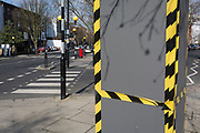 A tree protector encased in a wrapping of wood with hazard tape on a street corner of Elgin Cresent and Clarendon Road W11 in Notting Hill in the Royal Borough of Kensington and Chelsea, on 13th March 2018, in London, England.