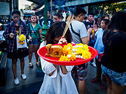 31 DECEMBER 2017 - BANGKOK, THAILAND: A woman prays while she holds up a tray of offerings on New Year's Eve at Erawan Shrine in Bangkok. Many Thais go to temples and shrines to pray and meditate during New Year's Eve and New Year's Day.    PHOTO BY JACK KURTZ