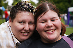 A portrait of a couple of women laughing together at the Nottingham Pride Gay Lesbian festival; held at the Arboretum,