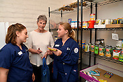 University of Arizona College of Nursing students review food labels with a Miracle Square resident at the pantry of the facility, where residents can supplement their food supply.  The nursing students work at the facility as part of the course work in Tucson, Arizona, USA.