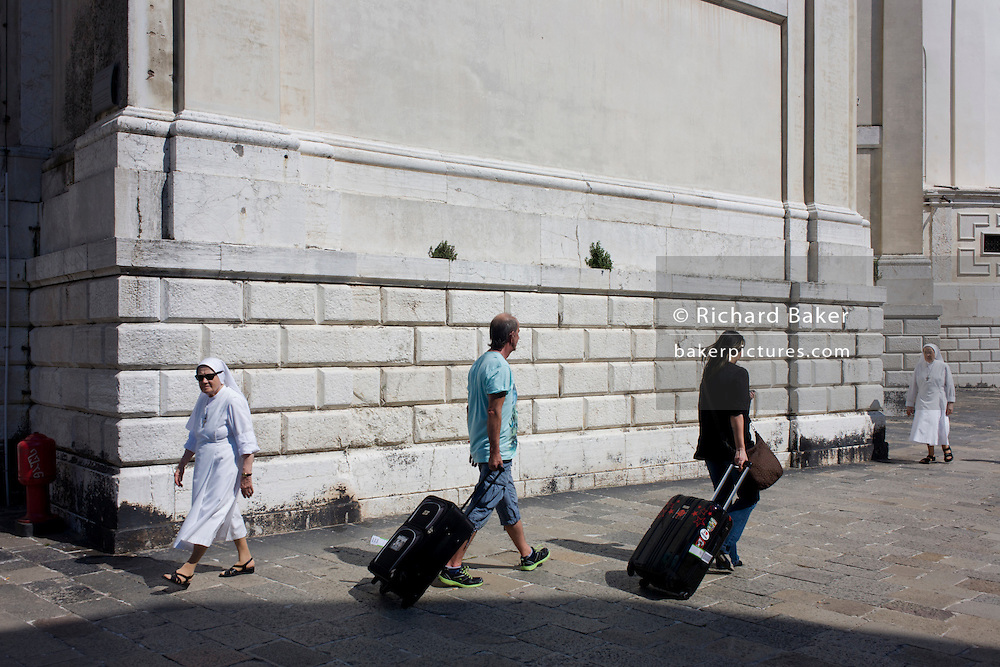 Two nuns walk past tourists with baggage in afternoon heat under the walls of Santa Maria della Salute church in Dorsoduro, a district of Venice, Italy.