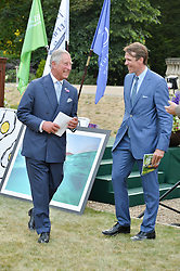 HRH The PRINCE OF WALES and BEN ELLIOT at the Quintessentially Foundation and Elephant Family 's 'Travels to My Elephant' Royal Rickshaw Auction presented by Selfridges and hosted by HRH The Prince of Wales and The Duchess of Cornwall held at Lancaster House, Cleveland Row, St.James's, London on 30th June 2015.