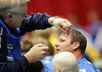 Håndball<br /> Fjerde runde i NM 2005<br /> Drammen HK v Fyllingen<br /> Foto: Morten Olsen, Digitalsport<br /> <br /> DHKs Svein Erik Bjerkrheim fikk et kutt over øyet. Her plastres han av lege Trond Hempel