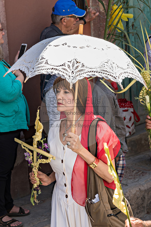 A Mexican woman carries a woven palm cross during a procession through the city center during Palm Sunday marking the start of Holy Week March 25, 2018 in San Miguel de Allende, Mexico. Christians commemorate the entry of Jesus into Jerusalem when it was believed that the citizens laid down palm branches in his path.
