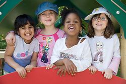 Group of children standing together on climbing frame smiling,